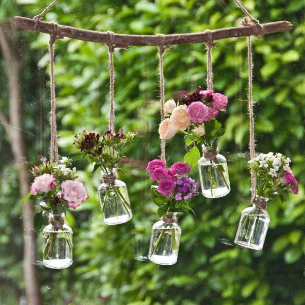 Houten tak met vijf flesjes en bloemen voor het raam